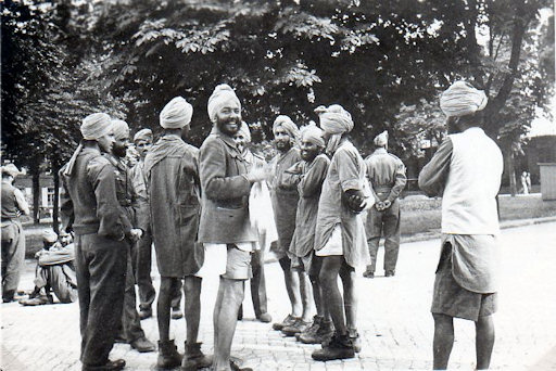 A Sikh soldier from the Legion (second from the left) speaks to a group of prisoners-of-war in an attempt to persuade them to join him.